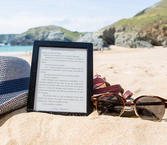 ebook on beach with hat and sunglasses