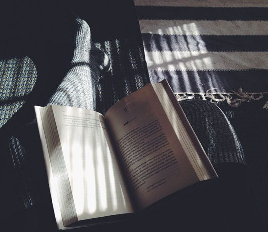 Person reading a book in soft light